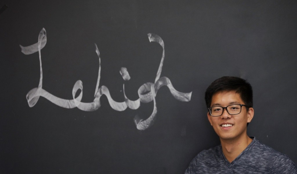 student in front of chalk board  with  the word Lehigh