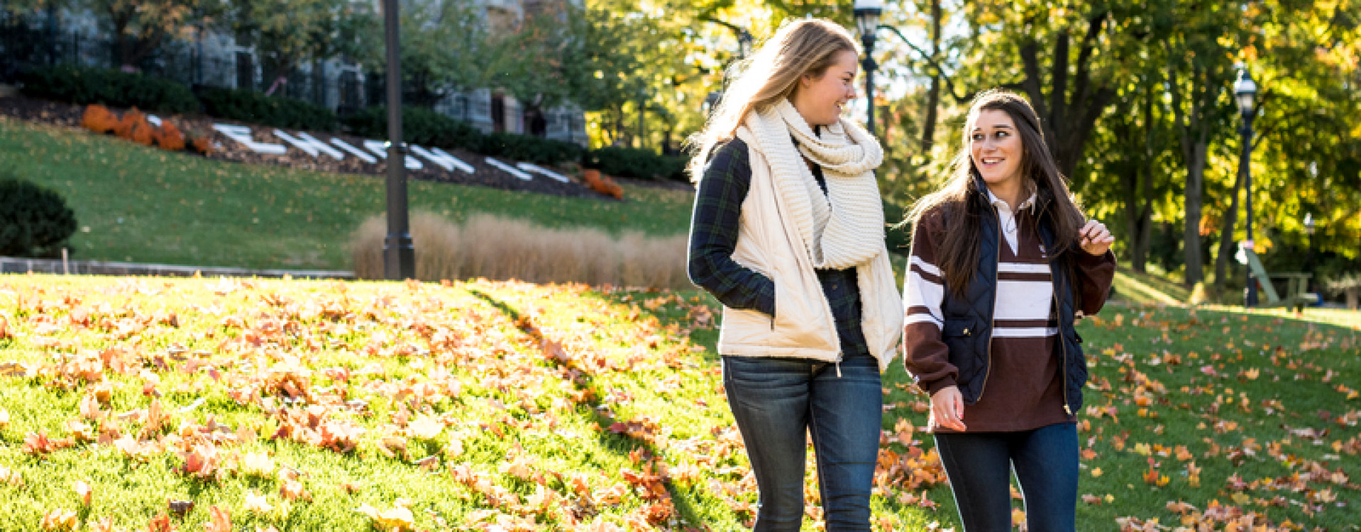 Two female students on the University Lawn in fall